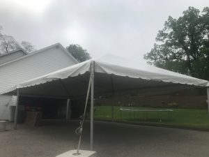 Looking under 20' x 40' frame tent next to a home for Graduation Party