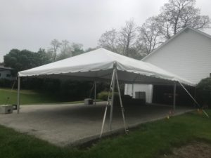 Stakes and deadweight on the 20' x 40' frame tent next to a home for Graduation Party
