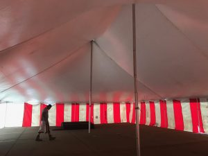 Under a 40' x 60' rope and pole tent with Red and White Sidewall used for Fireworks tent at Hy-Vee in Cedar Rapids, Iowa