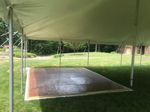 Under the 20' x 40' rope and pole tent with dancefloor for a wedding reception at a St John Vianney Church in Bettendorf IA