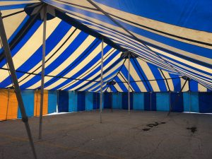 Under the Blue and White 40' x 70' Galla rope and pole tent setup for a fireworks stand in Davenport, Iowa