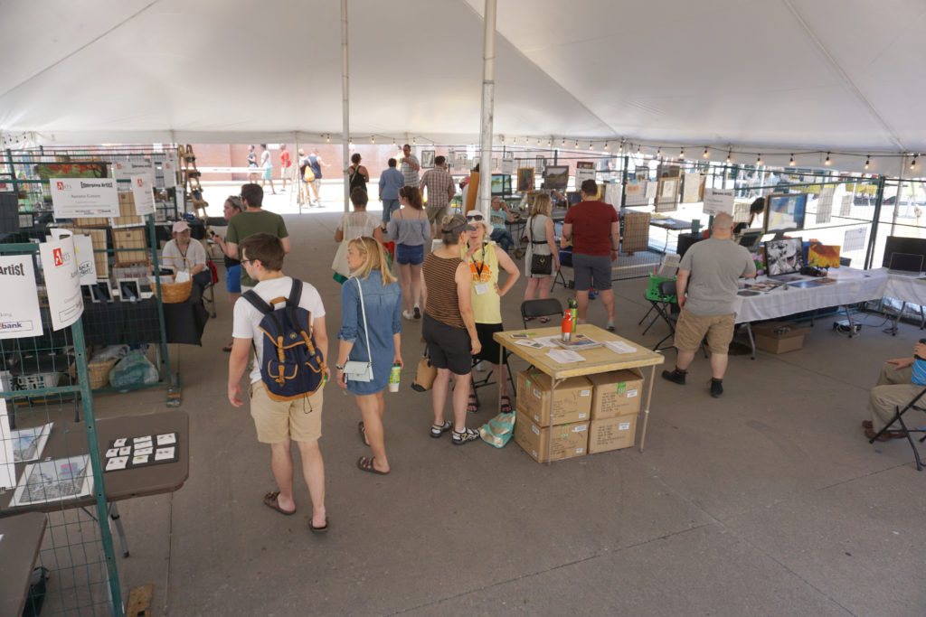 Under the student art exhibit tent at Summer of the Arts festival in Iowa City