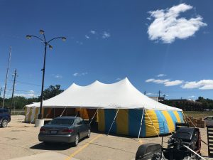 White top 30' x 60' rope and pole (one piece) tent for Kaboomers fireworks Des Moines, IA with blue and yellow side walls