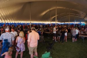 "People under the 60′ x 150′ ""twin pole"" Legend rope and pole tent at Blues and BBQ in North Libery, Iowa"