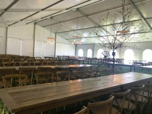 Under a 60' x 66' clearspan Losberger-made tent with tables and a tree