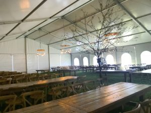 Under a 60' x 66' clearspan Losberger-made tent with tables and a tree from Town or Country Events