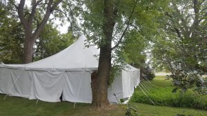 30' x 60' rope and pole wedding tent with white sides Monticello, IA surrounded by trees