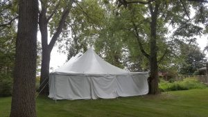 End of 30' x 60' rope and pole wedding tent with white sides Monticello, IA surrounded by trees