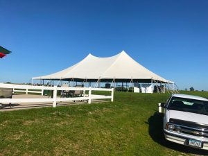 Outside of a white 60' x 90' rope and pole tent for a Wedding Reception in Newton, Iowa