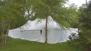 Side of 30' x 60' rope and pole wedding tent with white sides Monticello, IA surrounded by trees
