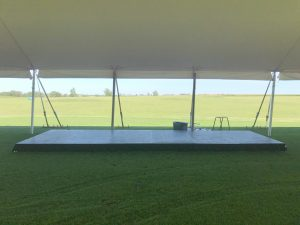 Small stage under the white 60' x 90' rope and pole tent