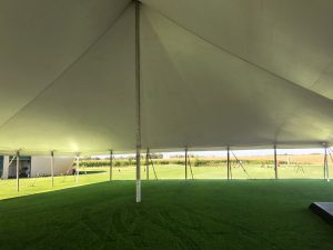 Under a White 60' x 90' rope and pole tent for an Outdoor Wedding & Wedding Reception in Newton, Iowa