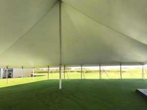 Under the white 60' x 90' rope and pole tent for a wedding reception in Newton, Iowa