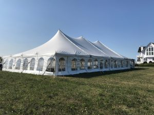Side of 40' x 80' rope and pole wedding tent setup in Fairfield, Iowa with building in the background