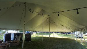 Under a 40' x 80' rope and pole tent with lights at a campground near Muscatine, Iowa